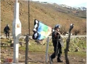 Un gendarme argentino se lleva la bandera de los Mapuches en un desalojo de un campo ocupado, en Neuquén.