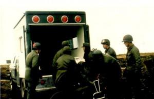 """""""Acá está nuestro grupo de Fuerza Aérea Argentina cargando a un herido en el aeropuerto de Puerto Argentino (BAM Malvinas), luego de uno de los bombardeos. Las F-250 habían llegado de Estados Unidos, ya totalmente equipadas, en el año '80. A mí me había tocado ir a retirar una 0km a El Palomar. Había 4×2 y 4×4, con motores de seis cilindros. A Malvinas se mandaron dos en Hércules, por supuesto 4×4, y dieron muy buenos resultados. Eran ambulancias realmente militares, ya que para el uso en ciudad, que durante año se les había dado, eran muy duras y poco confortables para los pacientes"""".(Dr.Daniel Oudkerk )"""